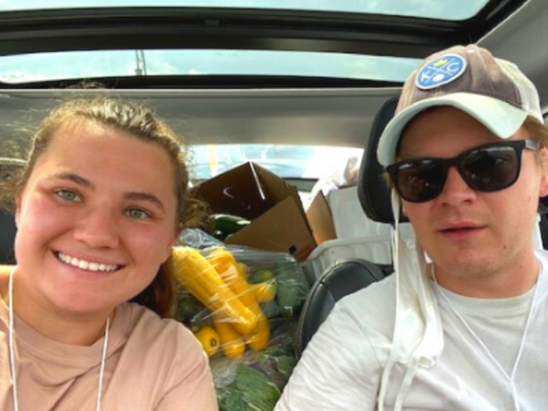 Couple in car with produce filling trunk