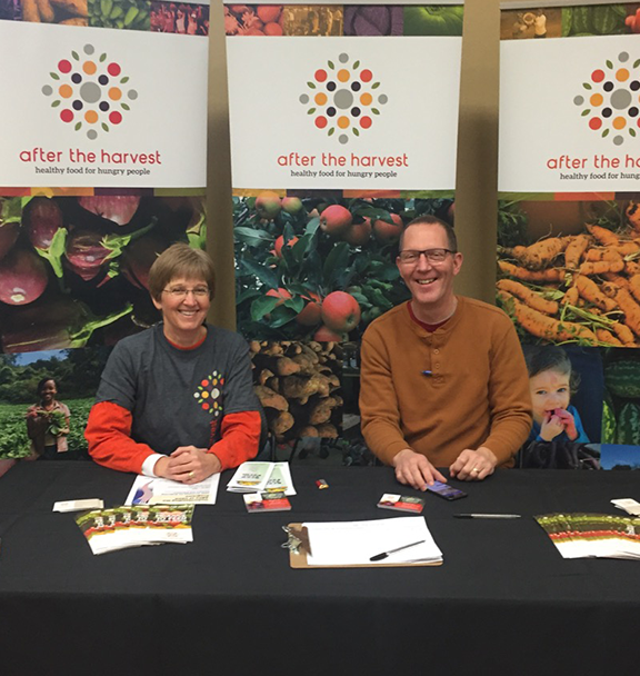 A man and woman who are yambassadors are sitting in an After the Harvest booth