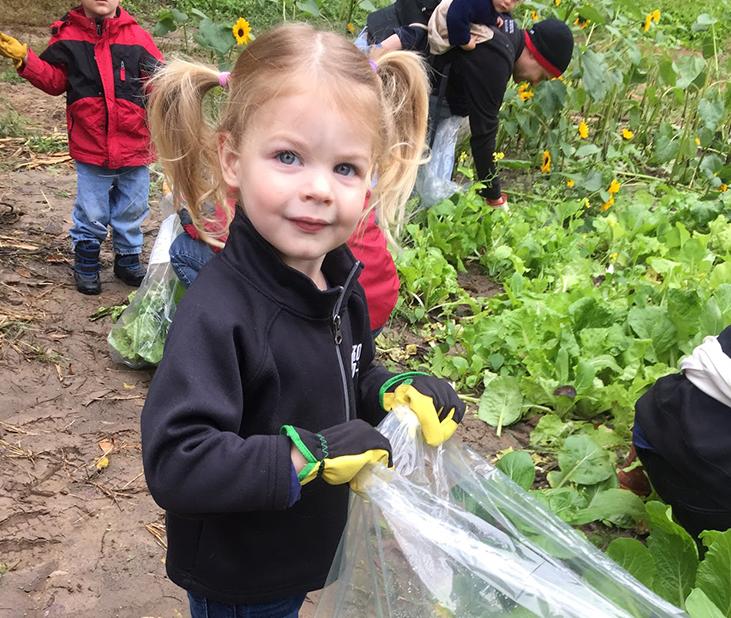 Little girl in gloves holding a plastic bag