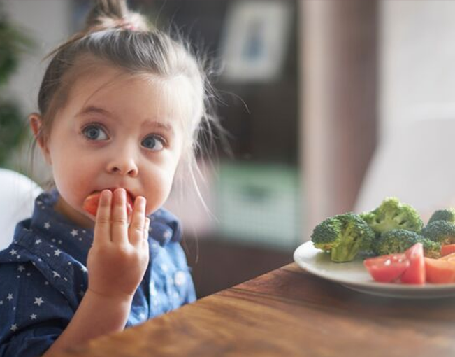 Little girl eating a tomato next to a table with a plate filled with broccoli and tomatoes