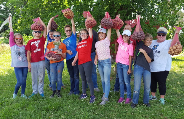 volunteers with freshly picked produce